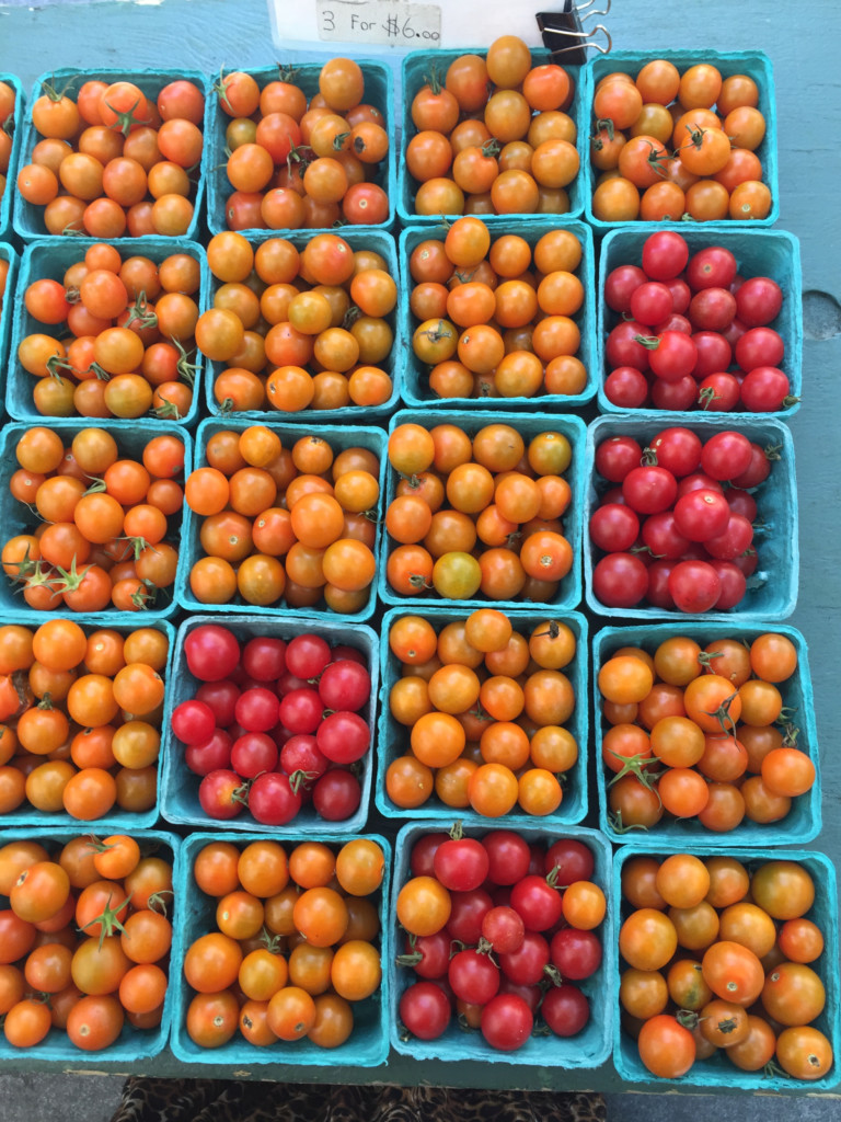 "The yellow cherry tomatoes are ""sun sugar tomatoes,"" and they are a vibrant orange when at their peak ripeness."