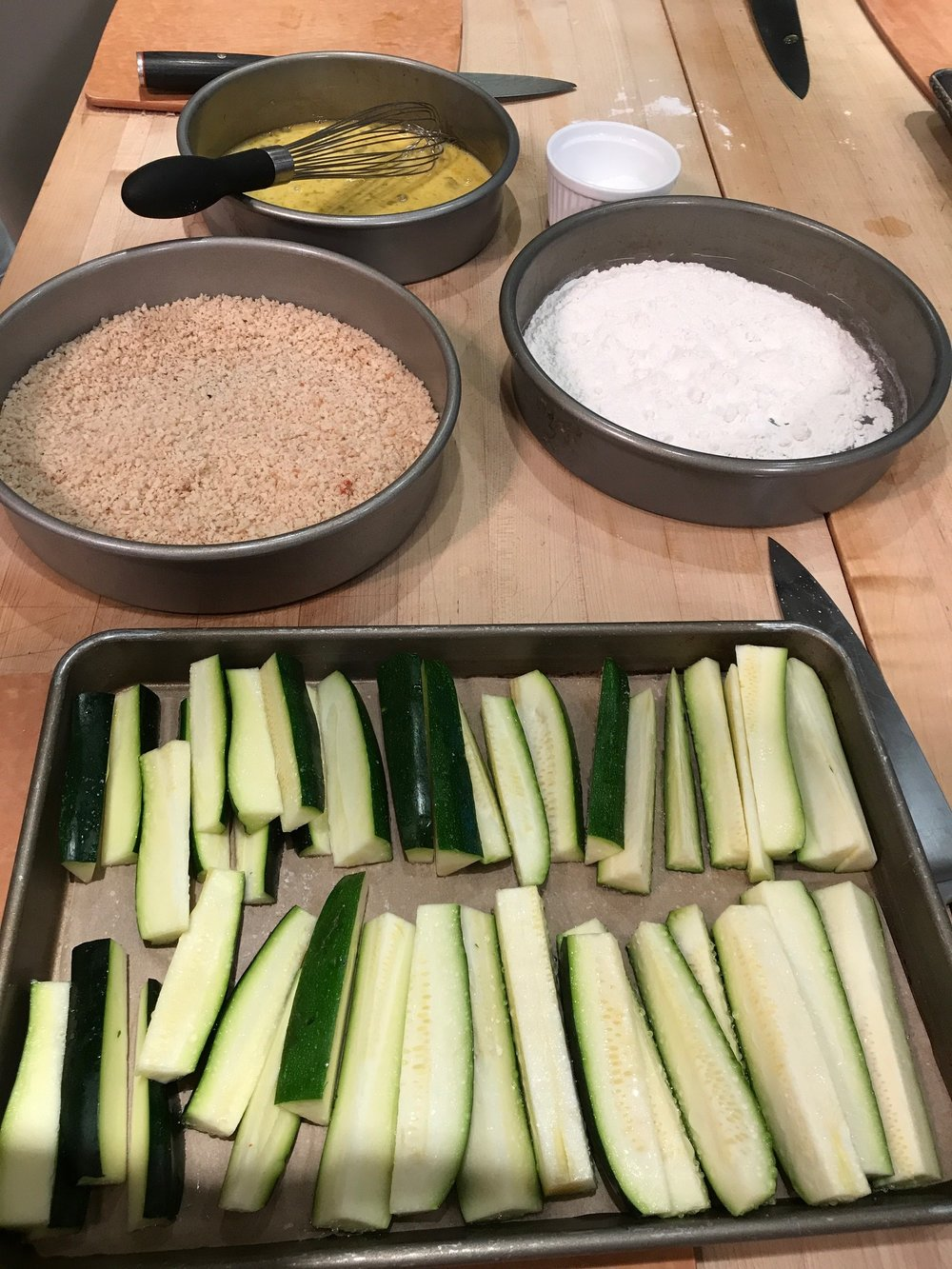"Let the zucchini ""sweat"" before dredging.  Use a paper towel to absorb the water the zucchini release."