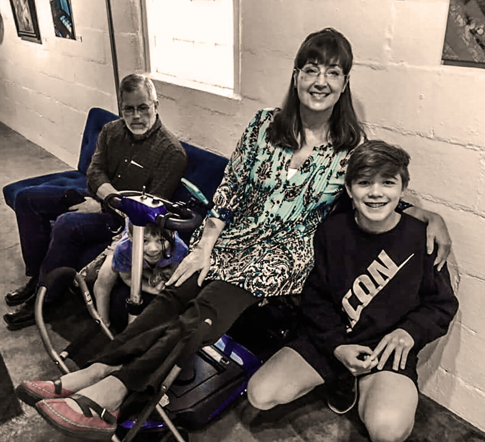 This is my favorite photo from a 2019 art gallery reception. I was pleased to be included among the featured artists. Before the doors opened, my daughter took this informal photo of my husband, two of our grandchildren (one of whom is peeking out from behind my mobility scooter), and me. I can sit up longer if I keep my feet elevated. People seem to be growing accustomed to being around the eccentric art lady who props up her feet. I find that if you are just genuinely yourself, most people will come to accept you as you are.