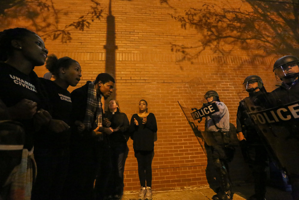 "Millennial Activists United leaders, Brittany (left) and Alexis, stand quartered off into a dark side street by St. Louis police during a nighttime protest; repeating the words of Asata Shakur 42 times in honor of the days since Mike Brown's death. ""It is our duty to fight for our freedom; it is our duty to win. We must love and support each other. We have nothing to lose but our chains."""
