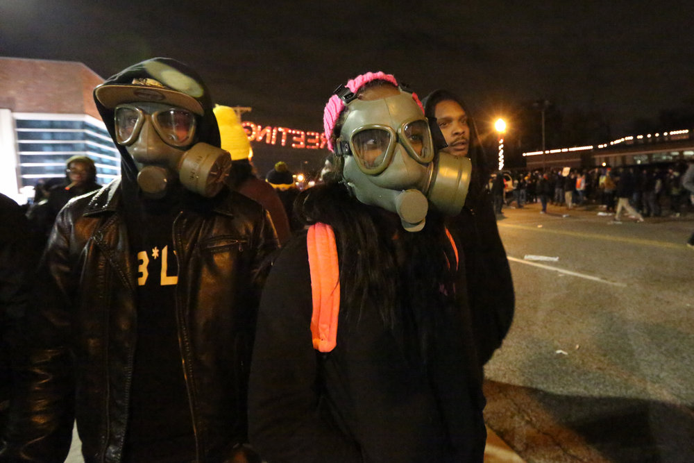 Having come prepared for the worst, T-Dub (left) and Rika practice putting on their gas masks in front of the Ferguson police department, waiting for the Grand Jury announcement in the case against officer Darren Wilson for the killing of Mike Brown.