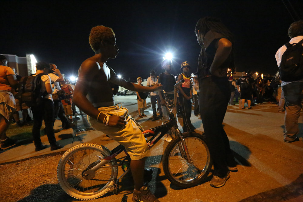 Young boys from the community come out to watch the protests on West Florissant in Ferguson, MO just days after Mike Brown's death.