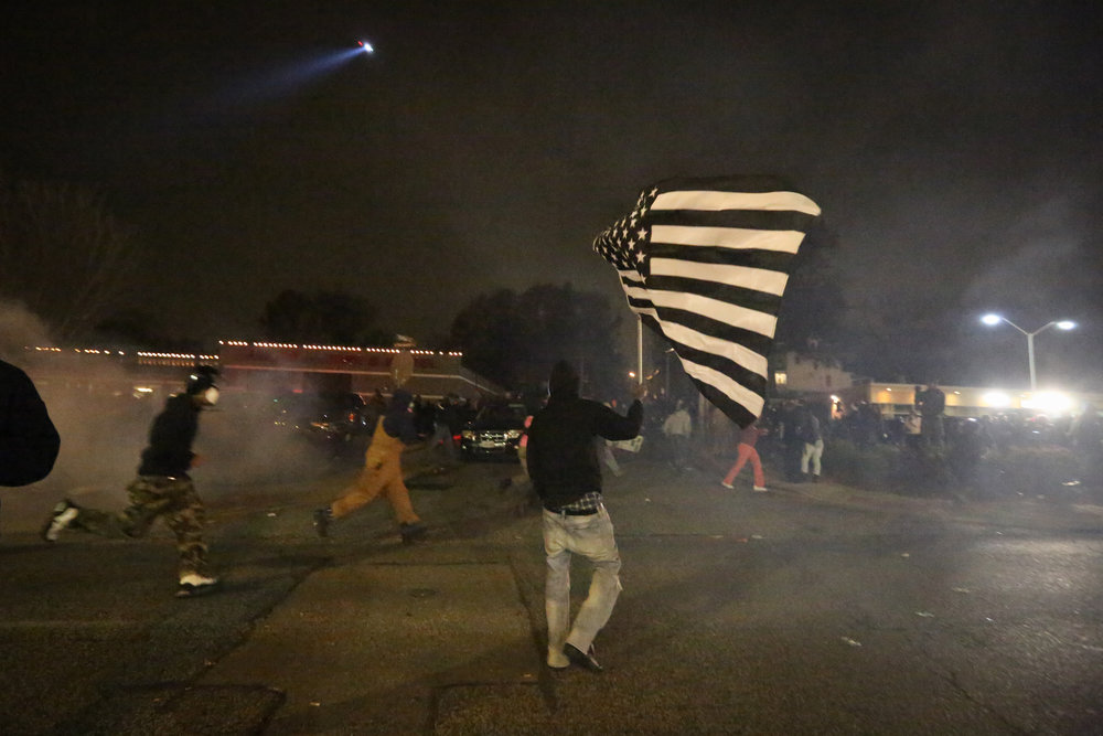 Teargas rains down on protestors in front of the Ferguson police department, as they protest in response to the non-indictment of officer Darren Wilson's in the killing of Mike Brown.