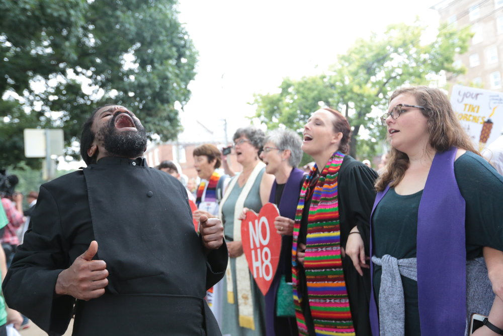 Author, musician and activist, Rev. Osagyefo Sekou (left) leads the line of clergy and community members in civil rights freedom songs as hundreds despite the jeering, taunts and racial slurs of white supremacists.