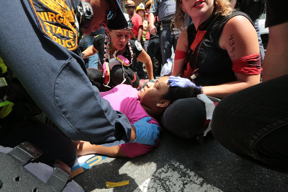 Street medics, militia and first responders rush to the aid of wounded scattered throughout three blocks of road - injured as self-professed neo-Nazi James Alex Fields Jr., 20, plowed through a crowd of nonviolent protesters. Hearing rumor that white supremacists were threatening a neighborhood  south of the mall, home to predominantly people of color, the protestors were headed towards the neighborhood when Fields violently attacked, killing Charlottesville resident Heather Heyer.