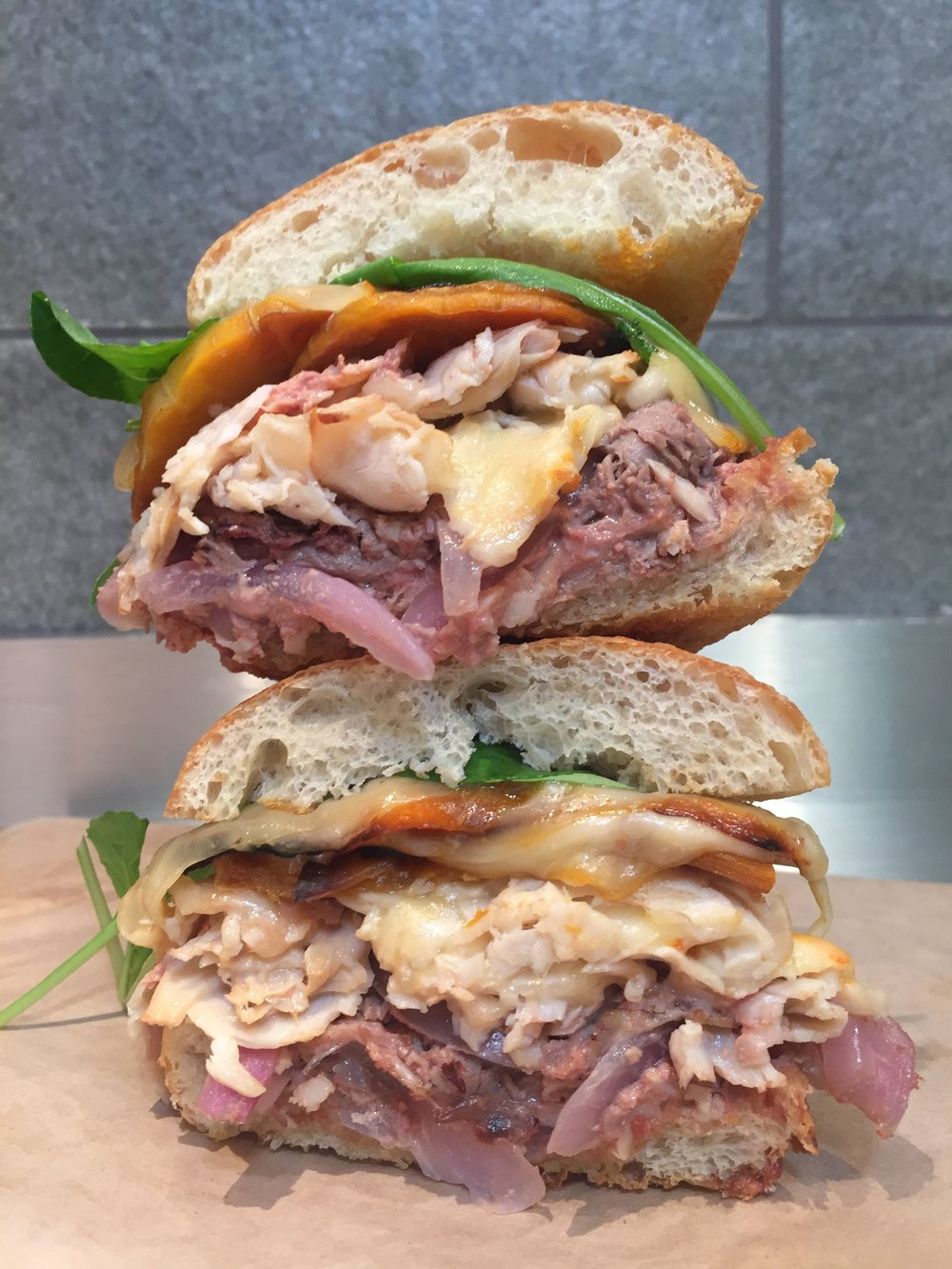 "THE BYGGYBIRD #3 :  ""The Turducken""  Toasted ciabatta, chicken liver pate, red onion, smoked duck breast, roast turkey breast, melted Muenster cheese, charred butternut squash, arugula, spicy pink mayo"