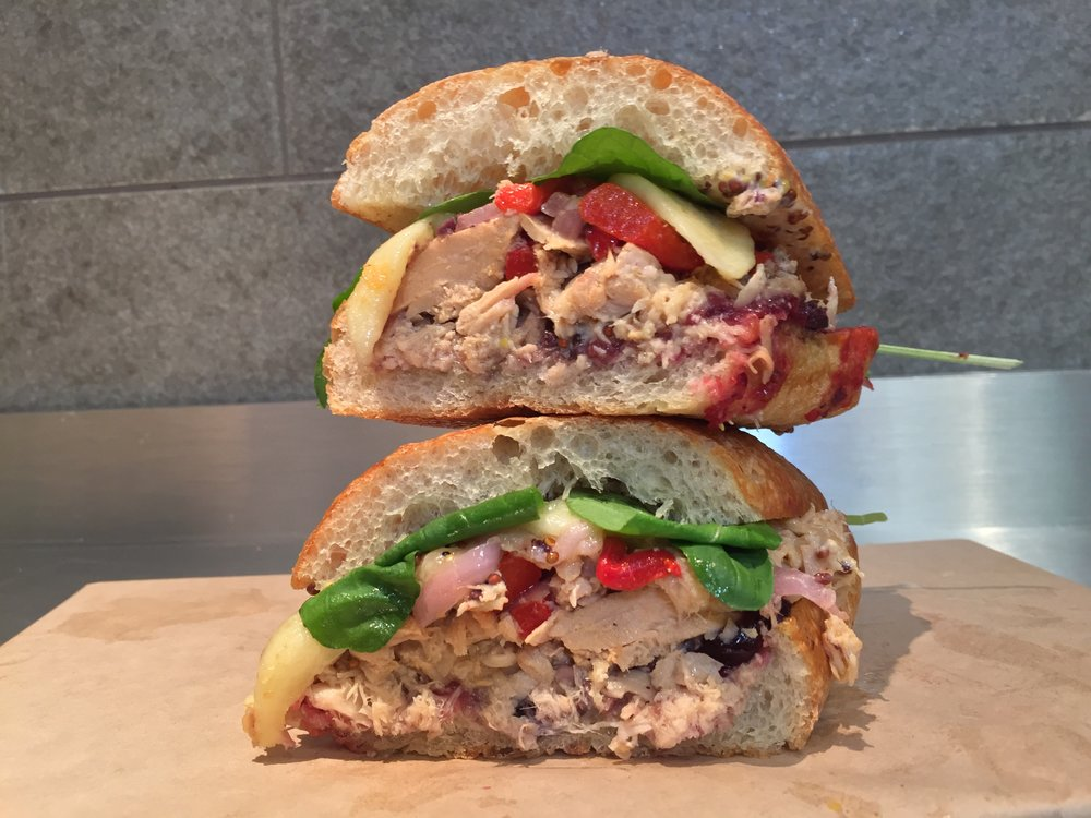 THE TUNA MELTY :  Toasted ciabatta, black olive tapenade, cranberry, USA wild Albacore tuna in extra virgin olive oil, roasted red peppers, red onion, melted Swiss cheese, baby arugula, creamy mustard
