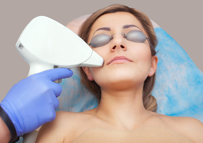 Patient receiving skin rejuvenation through laser treatments to reduce redness and pigmentation.