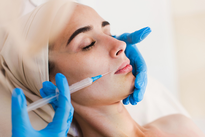 Dermatology patient receiving fillers into the skin to restore or increase volume to the face.