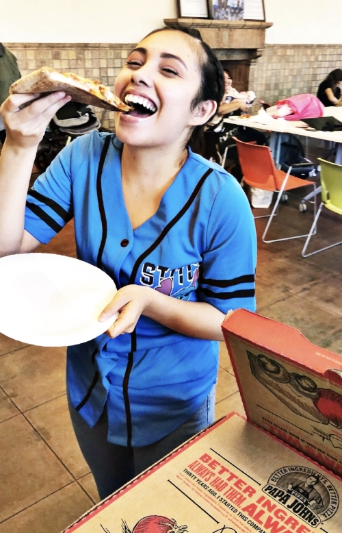 GenerationHer Member Karol Gutierrez, 19, enjoys a warm cheesy slice of Papa John's Pizza on June 2, 2018.