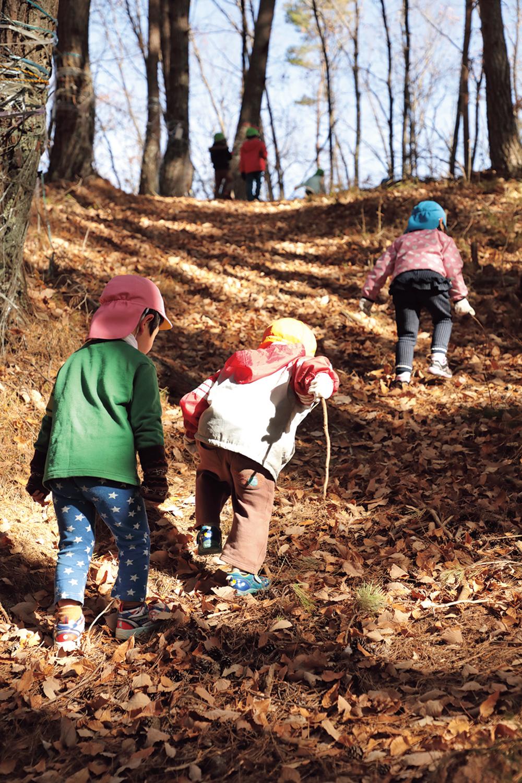 傾斜が急な山道を上手に登る子どもたち。小さい子の手を引く姿も