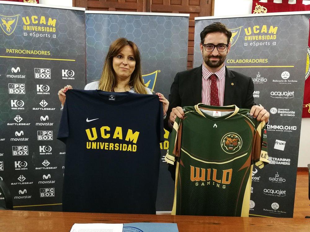 Blanca Chércoles, CEO de Wild Gaming y Samuel Mendoza, Director General de Infraestructuras y Desarrollo Digital de la UCAM, posan con las camisetas de UCAM y de Wild respectivamente. (Imagen: Wild Gaming)