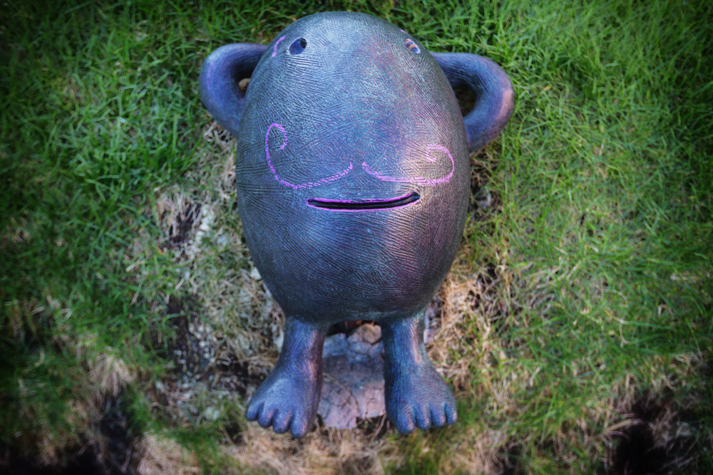 Rockman with a purple chalked mustache, a sculpture by Tom Otterness outside the Federal courthouse in Minneapolis