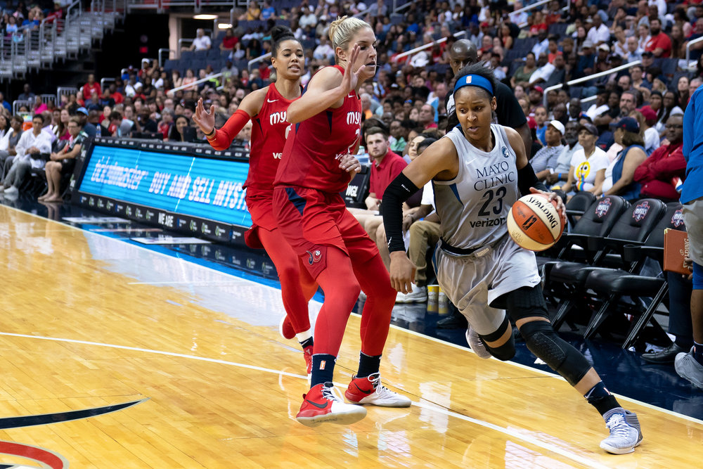 Maya Moore of the Minnesota Lynx dribbles around Washington Mystics Elena Delle Donne