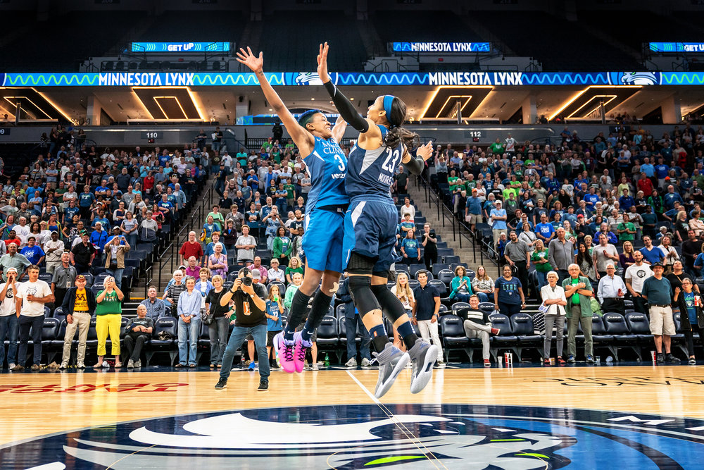 Danielle Robinson & Maya Moore celebrate a win against the Seattle Storm with a center court chest bump at at Target Center, Minneapolis.