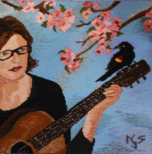 "APRIL  April is my birth month, so this tapestry is a bit of a 'selfie.' I had just learned to play ""Blackbird"" by the Beatles on my guitar, and the flowering crabtree in my yard was blooming. The tapestry is woven in wool, and is 18""x18"" and mounted on a frame."