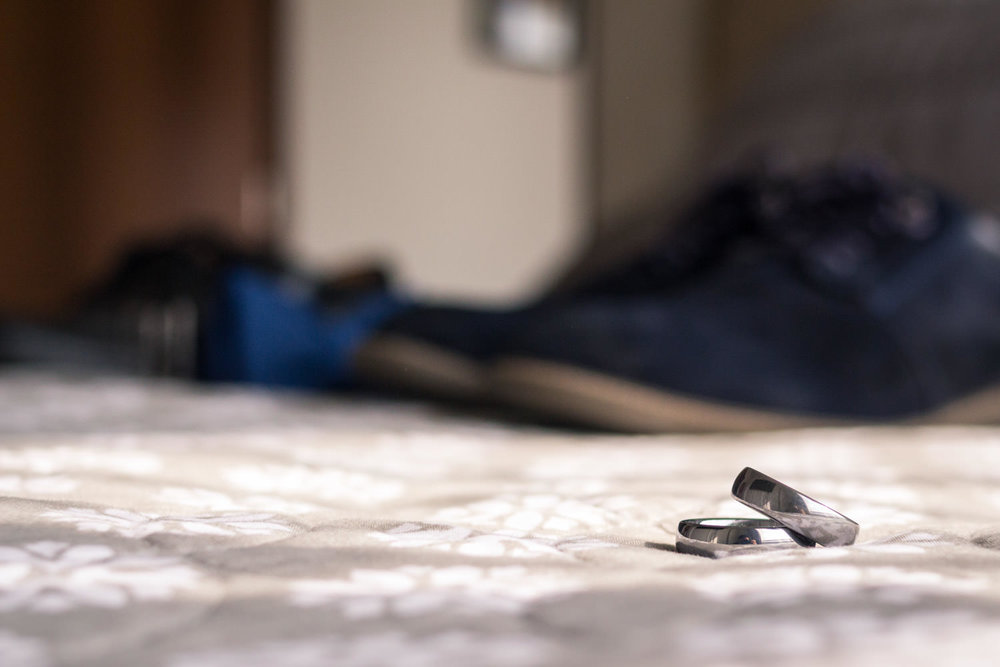 engangement rings on a bed with blue shoes