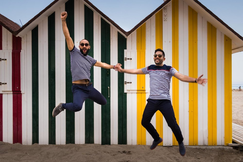 guys in love jumping in front of beach houses