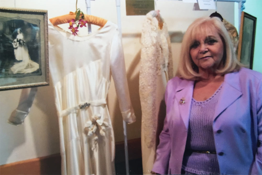 Past President of the IAHSRI, Claire Giannamore, standing next to Teresa Giannamore's (Claire's mother) wedding dress and photo. The Festa Della Donna event highlighted weddings of members and their ancestors.