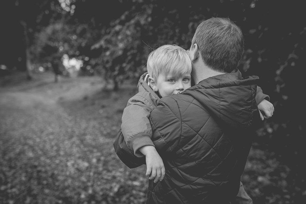 Little boy peeking over Dad's shoulder