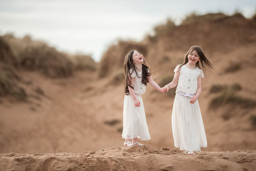 Sisters laughing on the sand dunes on Angus beach..jpg