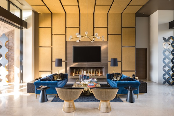 Artful symmetry prevails in the living area, where blue velvet Italia Chesterfield sofas and midcentury 18-karat gold wire and black velvet side chairs by Warren Platner for Knoll surround gold tree trunk coffee tables by RH Modern.