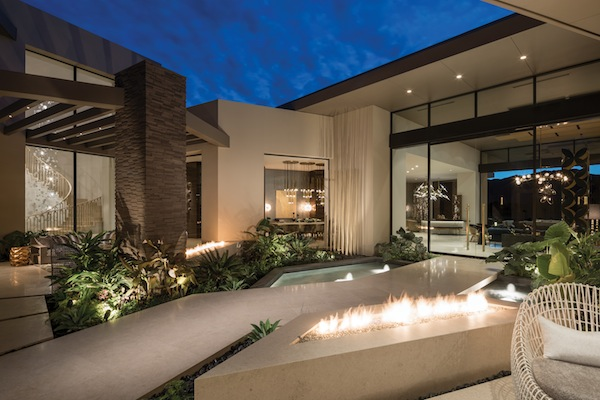 Fountains bubble and fire pits cast light along the courtyard walkway. A metal sculpture designed by Stein and built by Arc Forms to mimic bamboo moves in the breeze. The home's staircase, which curves around a long chandelier, is seen through the glass.