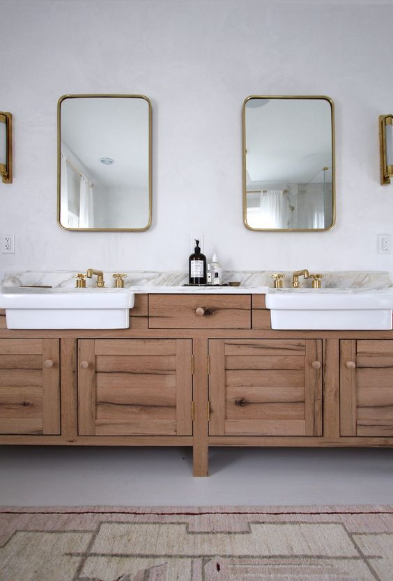 two farmhouse apron front sinks in the bathroom vanity with unlacquered brass