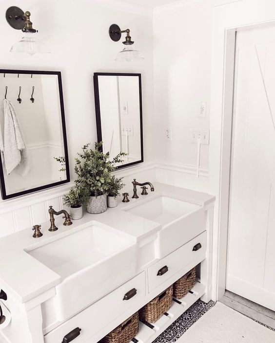white bathroom with cast iron apron front sinks in the vanity and oil rubbed bronze hardware, gooseneck widespread lav faucet