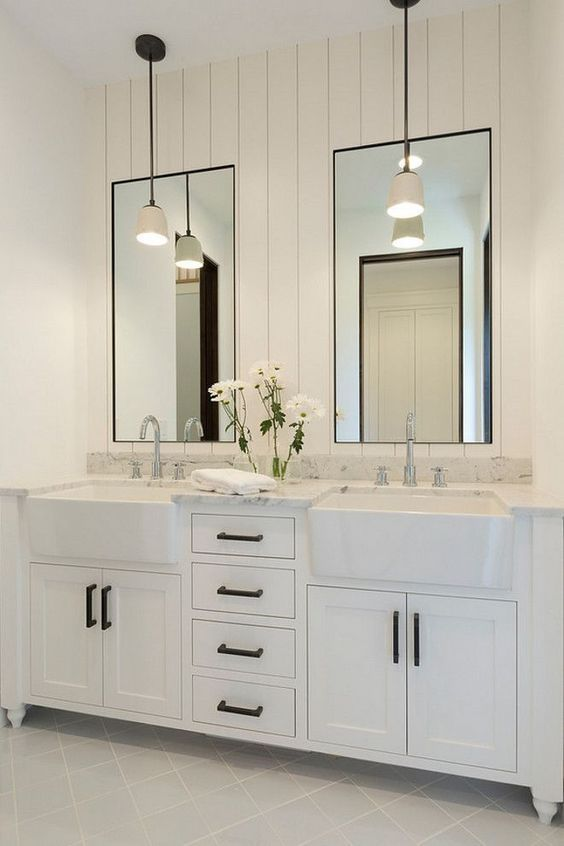 white bathroom with dual cast iron apron front sinks in vanity