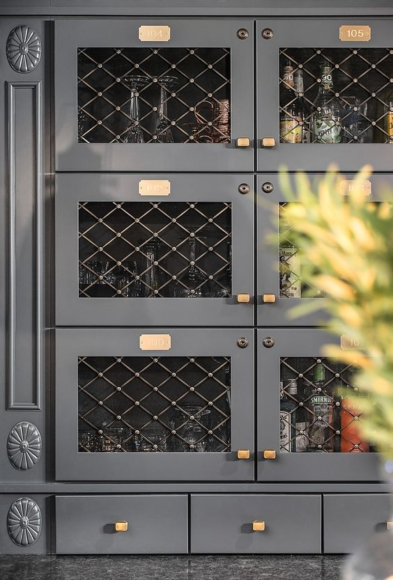 dark gray cabinets with brass hardware and wire mesh insert