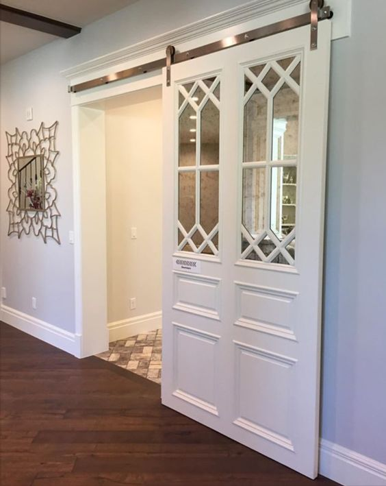 white sliding barn door with antiqued mirror and decorative mullion insert