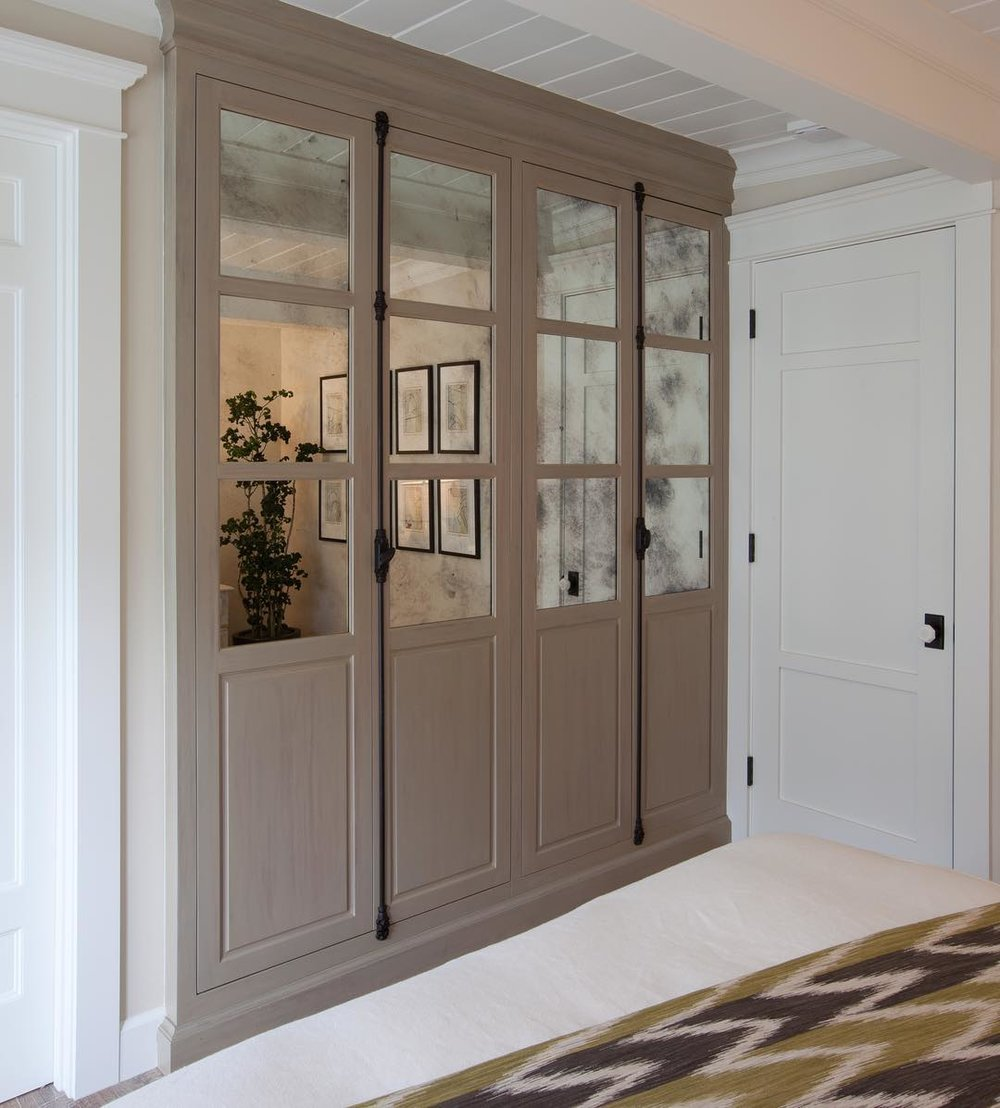 light gray wood inset cabinets with antique mirror and mullions with black cremone bolts