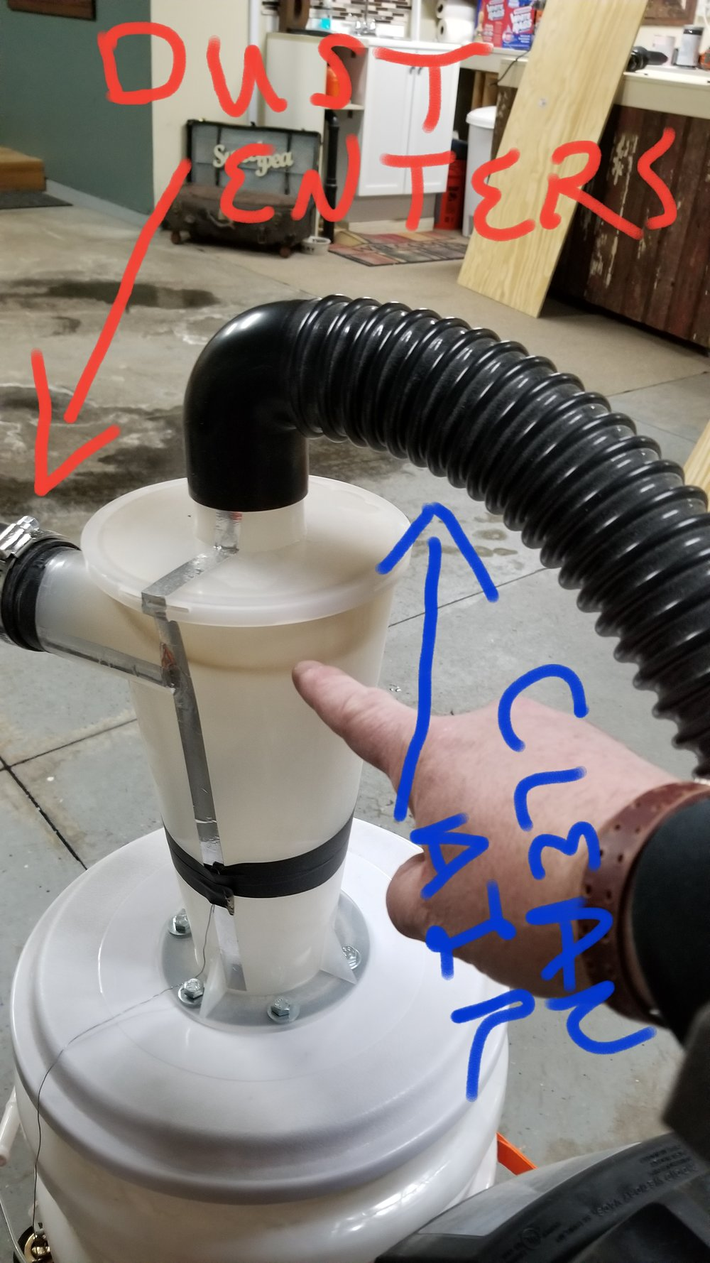- Here is the cyclone at work.  You can see the dust enters from the hose with the red arrow and pretty much anything that is heavier then air falls to the bottom. Then clean air (mostly clean air) enters your shop vac.  The blue arrow is showing that hose.  You rarely have to change out your shop vac filter!!  Side note: If you look along the left side of the funnel you will see metal tape and a thin metal wire.  The metal tape and wire (the wire goes down to the ground and drags on the ground) helps to ground the unit.  If you do not put those on, you may notice small pieces of dust collect all over the Dust Deputy and shop vac.  And, you may get small shocks when you touch either one of them.  Kind of like when you rub your feet on the ground and touch something metal. I recommend putting the metal tape and wire on the unit.