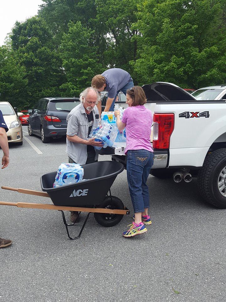 Tony McGuffin (holding the water) and other volunteers unload supplies on Memorial Day