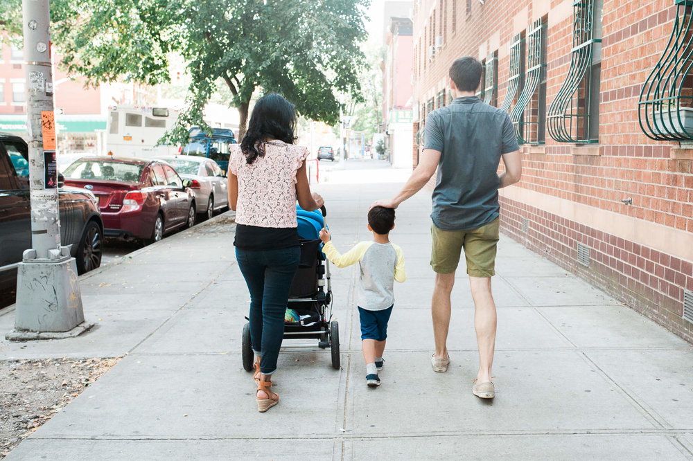 Family walking with stroller in Cobble Hill neighborhood Brooklyn New York family photographer lifestyle session in Cobble Hill by Lindsey Victoria Photography