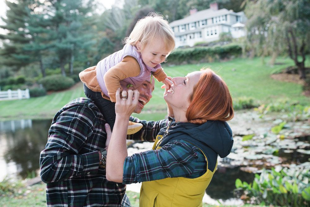 fall family photo little girl on daddy's shoulders reaching to kiss her momma in Litchfield County CT photo by Lindsey Victoria Photography
