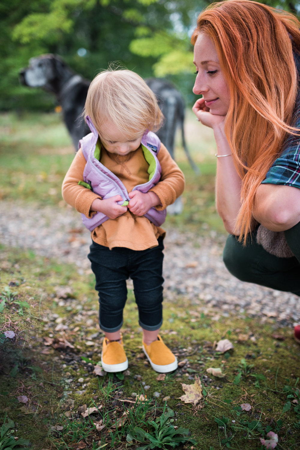 fall family picture toddler zipping her vest while her mother looks on in Washington CT photo by Lindsey Victoria Photography
