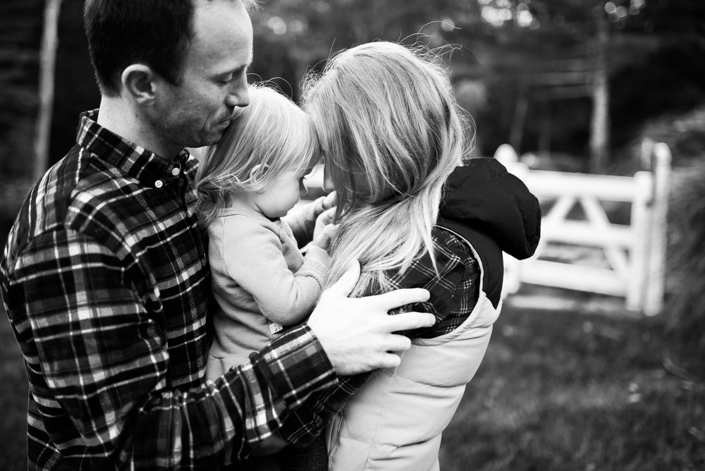 family photo daddy and mommy hugging daughter by Lindsey Victoria Photography black and white Washington CT