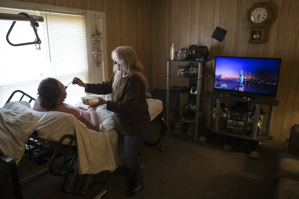 "Tammy Wise, right, feeds dinner to her disabled husban, Robby Wise, inside their home in Pleasant Ridge. The couple first met in the first grade. Later in life, Robby pursued Tammy for over a year, often leaving her $10 and $20 dollar tips where she bartended. The couple have been together now 16 years, but for the last three, Robby has been bed ridden with multiple sclerosis. ""I told her in the parking lot at the doctor's office that she could go on with her life,"" Robby said, recalling the diagnosis. ""Any other woman would have run off."""