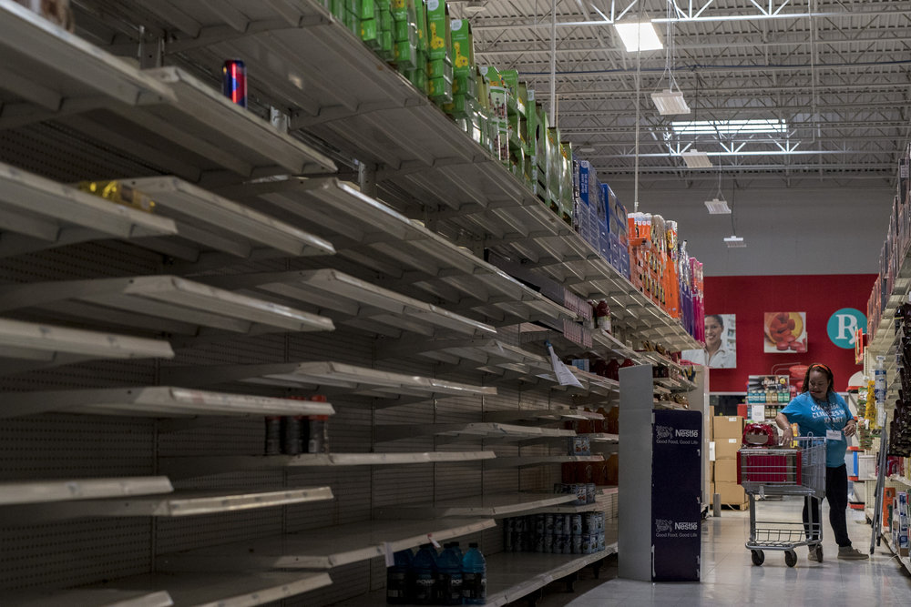 "A K-Mart employee restocks shelves in an aisle where shelves for water, gatorade and other drinks sit bare in the Vega Alta municipality of Puerto Rico. ""We get two pallets brought in of water here, two pallets there. There's just not enough,"" manager Hiram Jiminez said. ""Everybody needs water. They bring it in and it disappears."" Oct. 15, 2017"