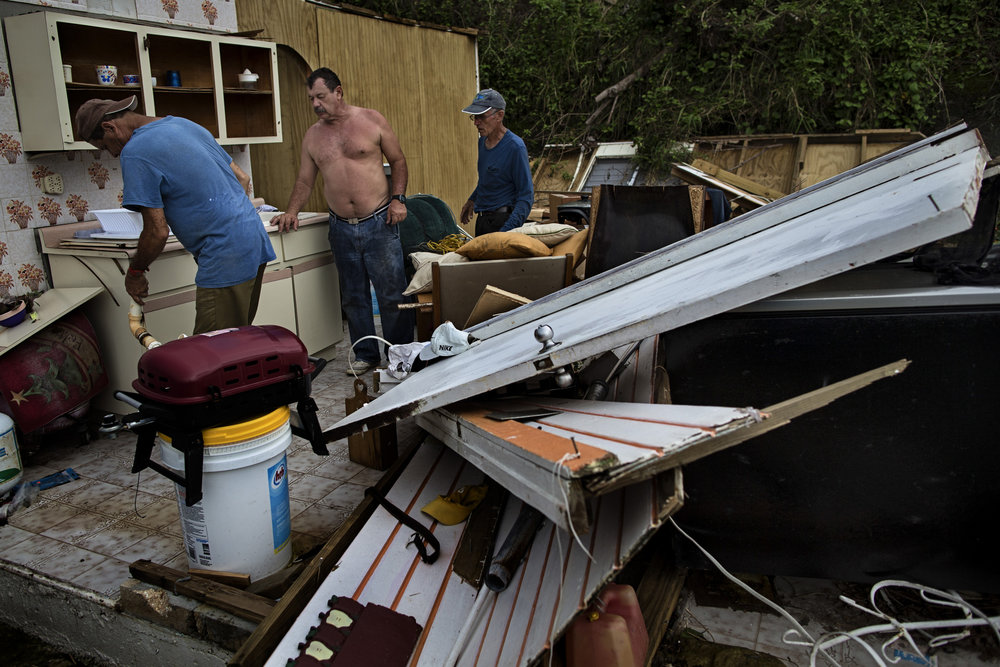 "Neighbors help Daniel Cruz Pagan, center, a resident in barrio Bozas in the Cialés municipality of Puerto Rico, a mountainous area hit hard by Hurricane Maria, move his kitchen sink to another area still useable in what is left of his home following the category 4 storm hitting the area three weeks ago. ""I stayed because a part of my home is concrete. I thought we would be safe,"" Pagan said. Pagan and his family did indeed survive the storm, but all of the roof and parts of the home constructed with wood, were destroyed. The family is now living in the few rooms spared from the storm and are looking to move as much of their home that is left into these areas. Oct. 11, 2017"