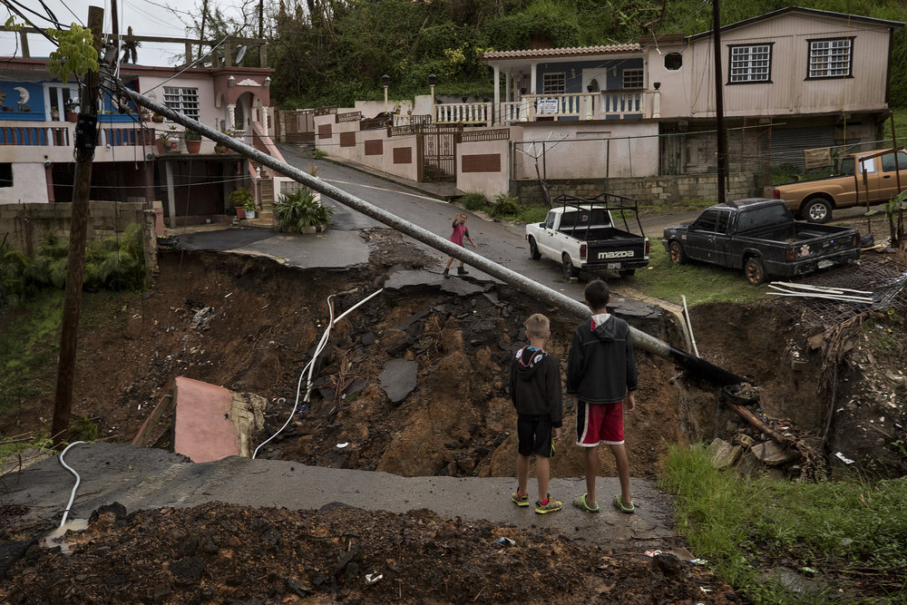 Children in the barrio La Loma neighborhood of the Barranquitas municipality of Puerto Rico yell across a washed out road in the community. Normally able to meet up to play, as typical neighbors, the children are now divided by a large gap after the small creek in the mountainous area swelled into a large river, wiping out the entire roadway. Damage to roadways across the island has proved to be a challenging obstacle for delivering aid and supplies to residents, particularly in the mountainous interior. Oct. 16, 2017