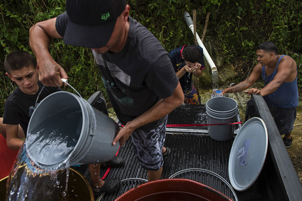 Fabian Robles, from left, Javier Robles, Caleb Maysonet, and Joe Maysonet drink and fill up large trash cans with water from a drainage pipe off Highway 149, connecting Manati to Ciales. The men and numerous other residents form lines at the mountain drainage pipes each day to take back to their communities where most are still without water and power three weeks after Hurricane Maria. Reports estimate that one million Puerto Ricans, out of its 3.4 million residents, are without reliable drinking water and at risk of cholera and diarrheal diseases if relying on surface water sources. Oct. 11, 2017