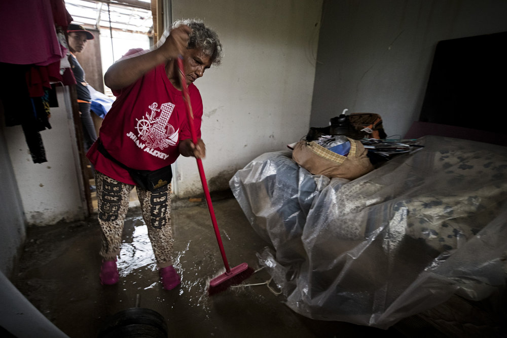 "Aná Ortiz, 56, attempts to sweep rain water from a heavy storm out of her home in Barranquitas where nearly a month after Hurricane Maria, she has only two livable rooms left. ""I wrap my bed and items in plastic to keep them protected. I receive a tarp from a handout, but it isn't enough to cover my roof,"" Ortiz said. Ortiz has only two rooms left in her home that still have a roof covering the interior, but even those areas are leaking. Oct. 16, 2017"