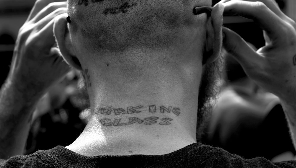 "A white supremacist with ""Working Class"" inked into his neck watches anti-fascist counter-protest Saturday, April 29, 2017, in Pikeville, Ky. Several groups, most from outside the region, counter protested most of the day, shutting down the city."