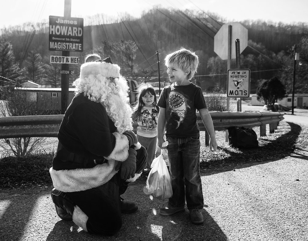 Jordan Howard, dressed as Santa Claus, talked with Kedan Matthews, age 5, after handing him Christmas gifts. In background is Lexy Brown, age 3. Howard filled in for his father Mike in the roll of the Mountain Santa, in Harlan County.