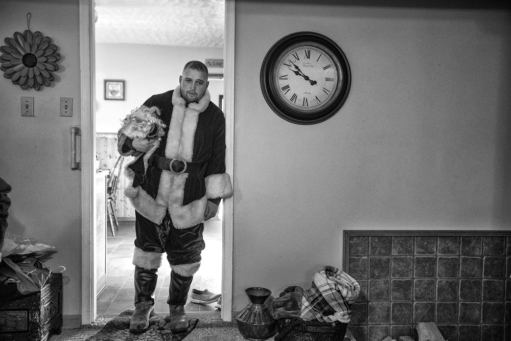 Jordan Howard stood in a doorway of his parent's home after delivering Christmas gifts to the children of Harlan, County. Dec. 16, 2017. Howard filled in as the Mountain Santa for his father Mike, who is terminally ill with lung cancer. Dec. 16, 2017.