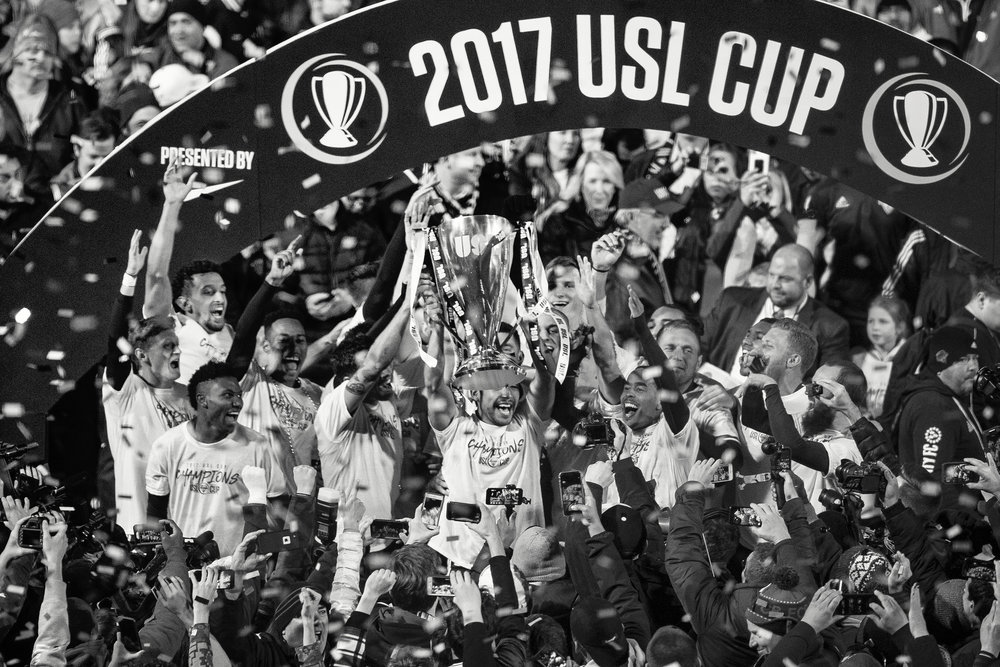Louisville City FC player Oscar Jiminez holds up the USL Cup as the team celebrates winning their first championship 1-0 against the Swope Park Rangers on Monday evening at Louisville Slugger Field. Nov. 13, 2017