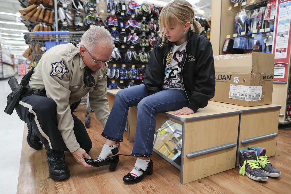 "Powell County Sheriff's Office employee Mike Townsend, left, helps Clair Beaty, 9, try on a pair of high heeled shoes at the Wal-Mart Supercenter in Winchester, Kentucky on Thursday during the ""Shop with a Cop"" event. The Red River Gorge Fraternal Order of Police Lodge 70 has been putting on the event for 18 years and has spent over 150 thousand dollars on 1500 children since it began in 1999. ""It's just interaction with the kids. You have good and bad experiences with some of their families,"" Townsend said. ""I once arrested this little girl's mother, but she still always says hi to me at her school. You want to have a good relationship with the kids."" Dec. 7, 2017"